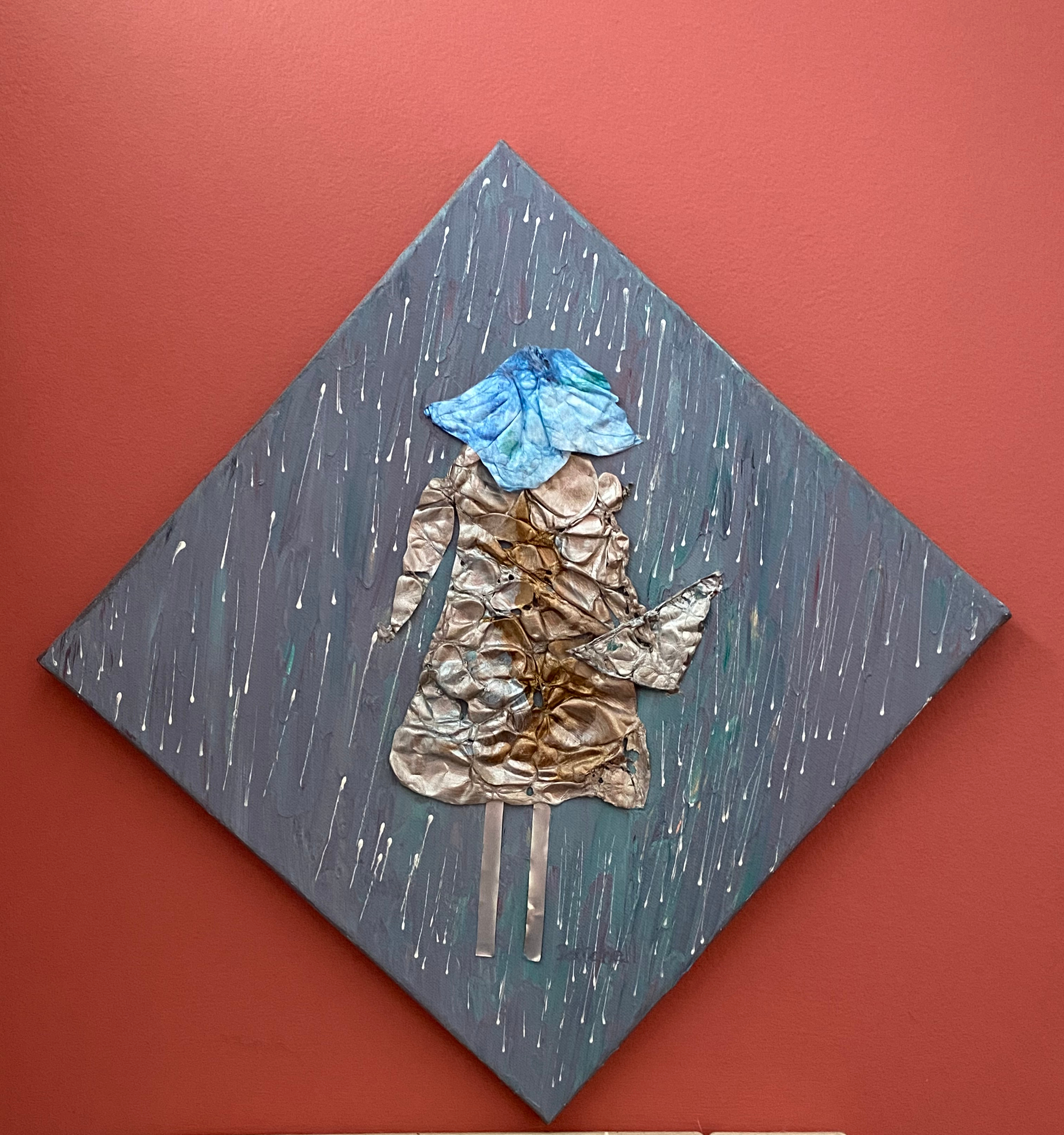 Rainhat Lady is a collage / assemblage work on canvas by Maura Satchell using found objects and created textures.